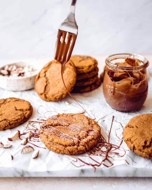 drizzling milk chocolate on malt ball cookies