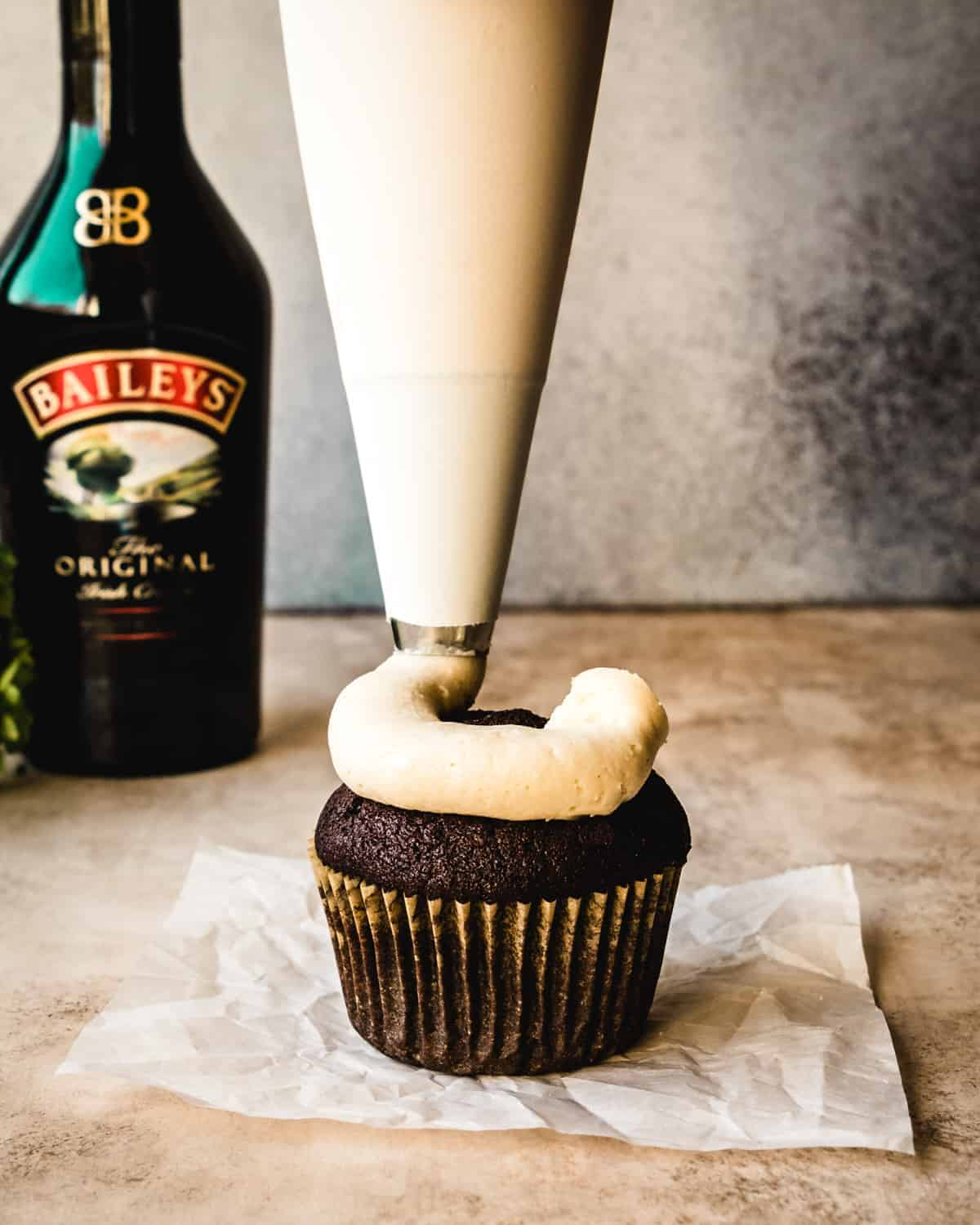 piping baileys buttercream onto a chocolate cupcake