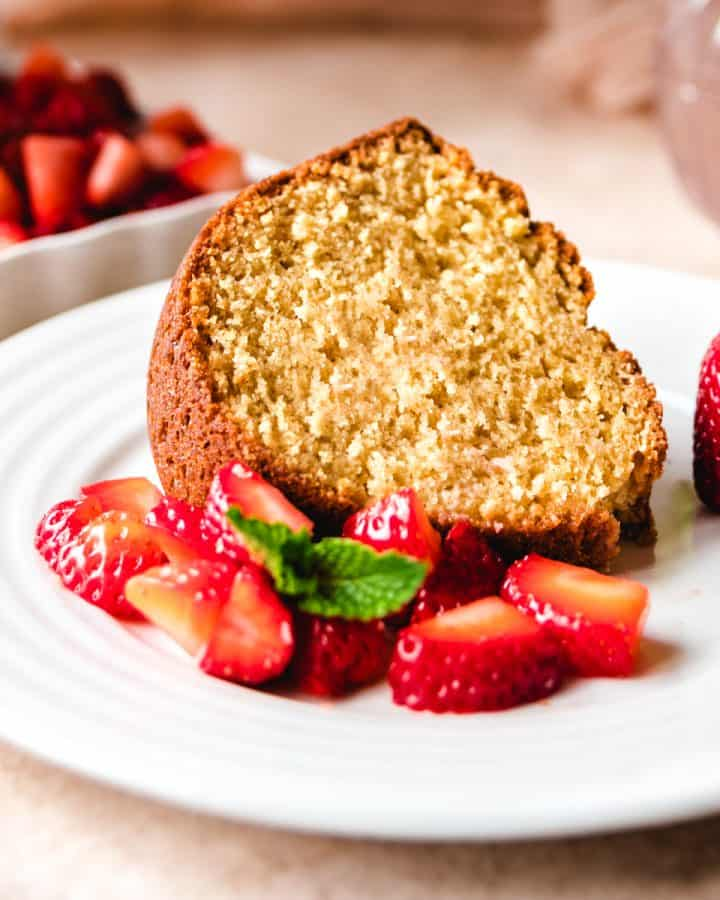 brown sugar bundt cake slide on a plate with strawberries
