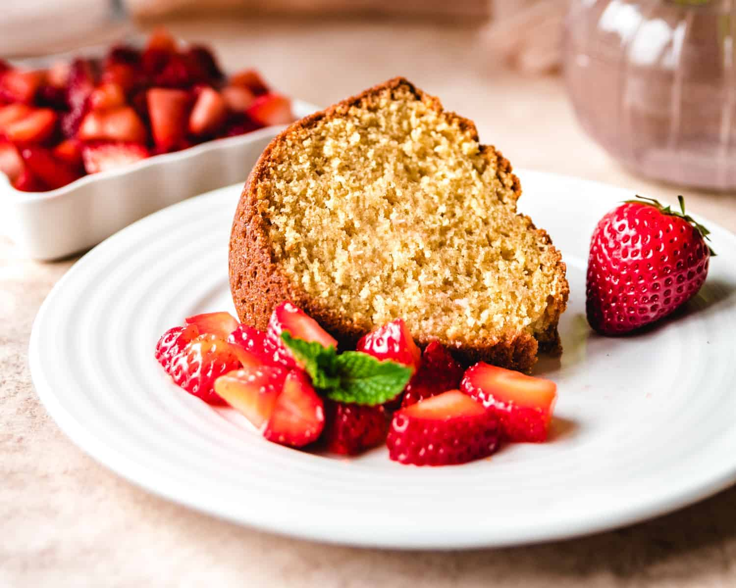 brown sugar bundt cake slide on a plate with strawberries