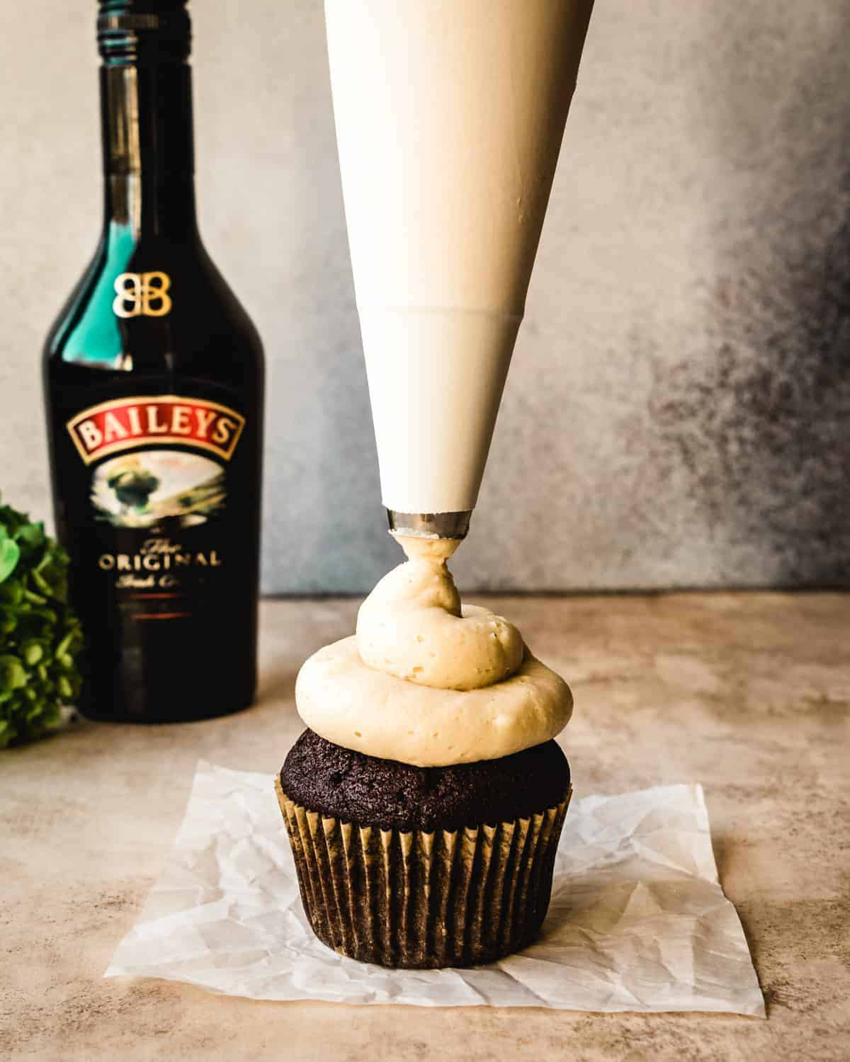 piping baileys buttercream frosting onto a chocolate cupcake