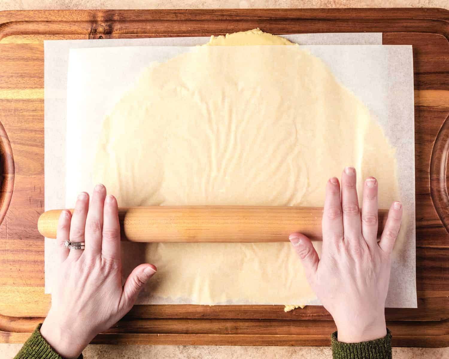 rolling out cookie dough between two sheets of parchment paper