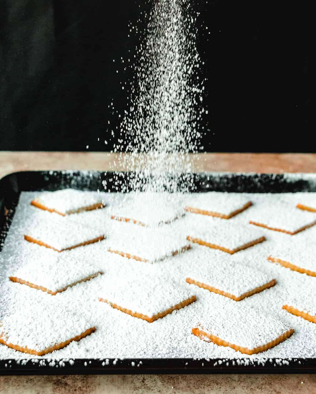 sprinkling powdered sugar over kourabiedes