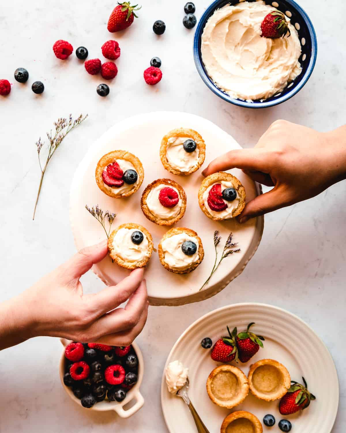 two hands grabbing for sugar cookie fruit tarts off a cake stand