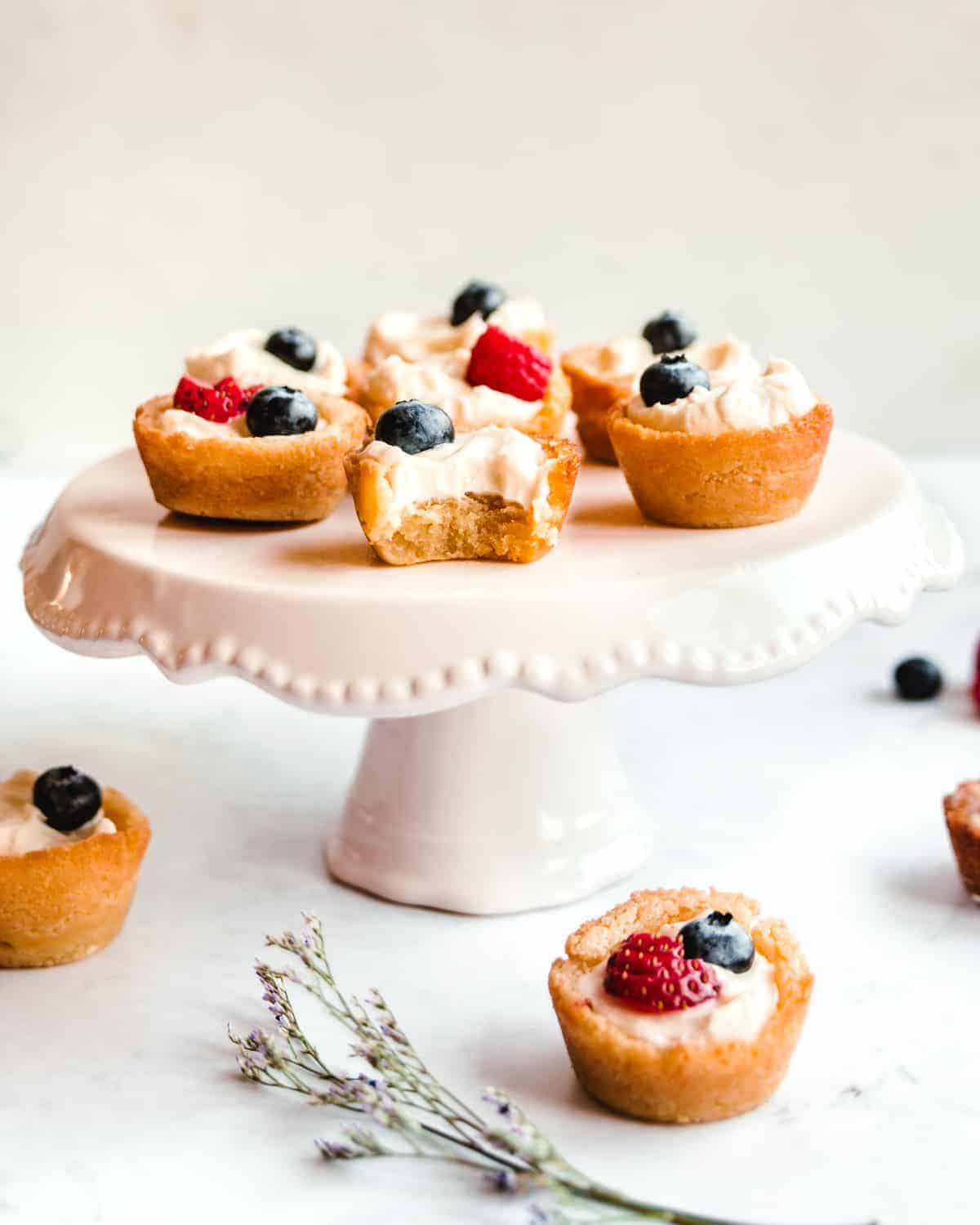 sugar cookie fruit tarts on a cake stand with bite taken out