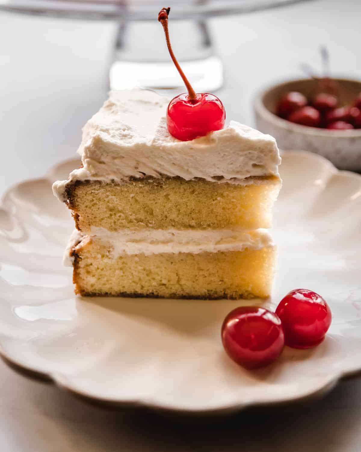 single slice of almond layer cake on a plate with maraschino cherries