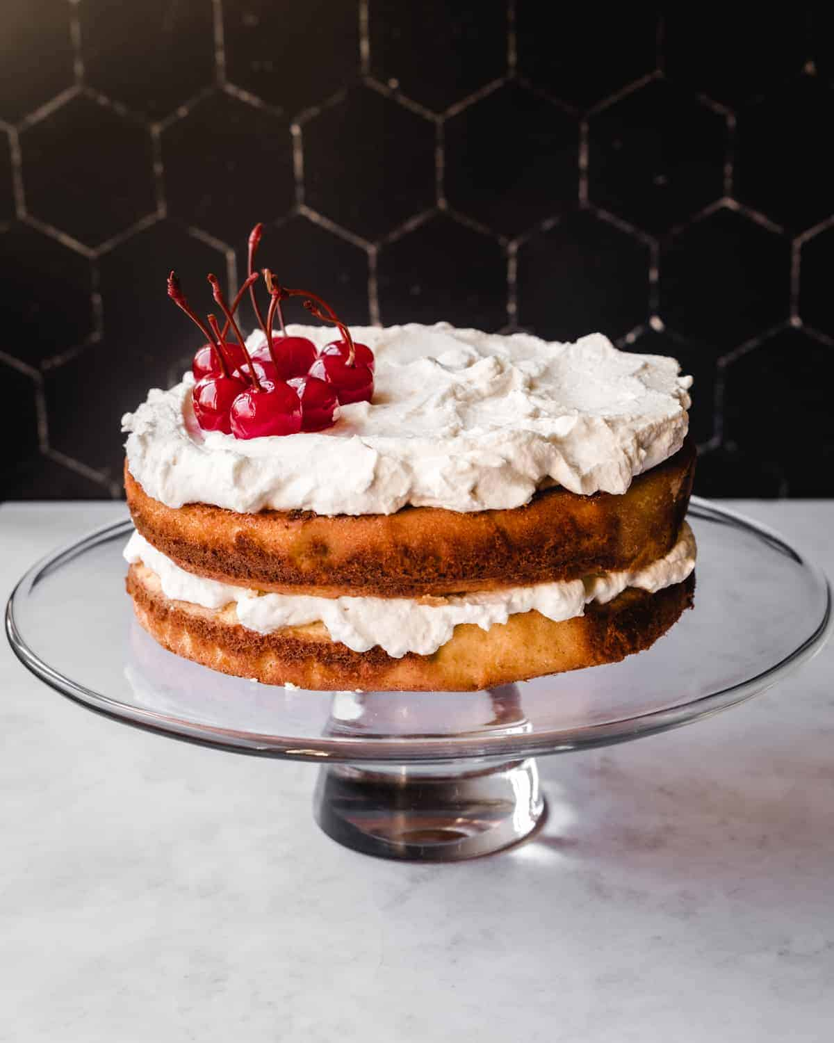 almond layer cake with cherry whipped cream on a glass cake stand