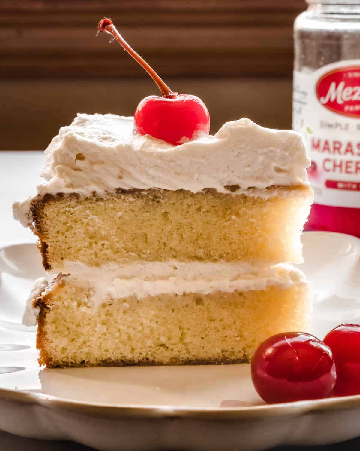 close up of a slice of almond layer cake on a plate with cherry whipped cream