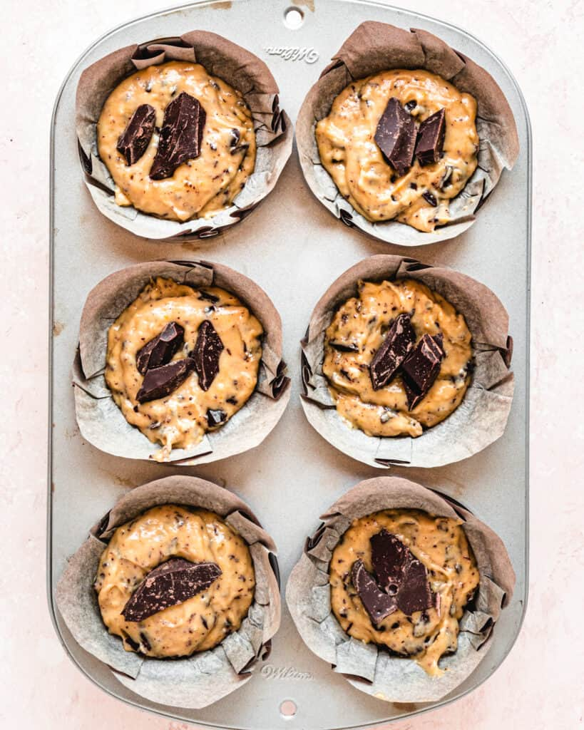 chocolate chip muffin batter in paper liners with chocolate pieces on top in a metal pan