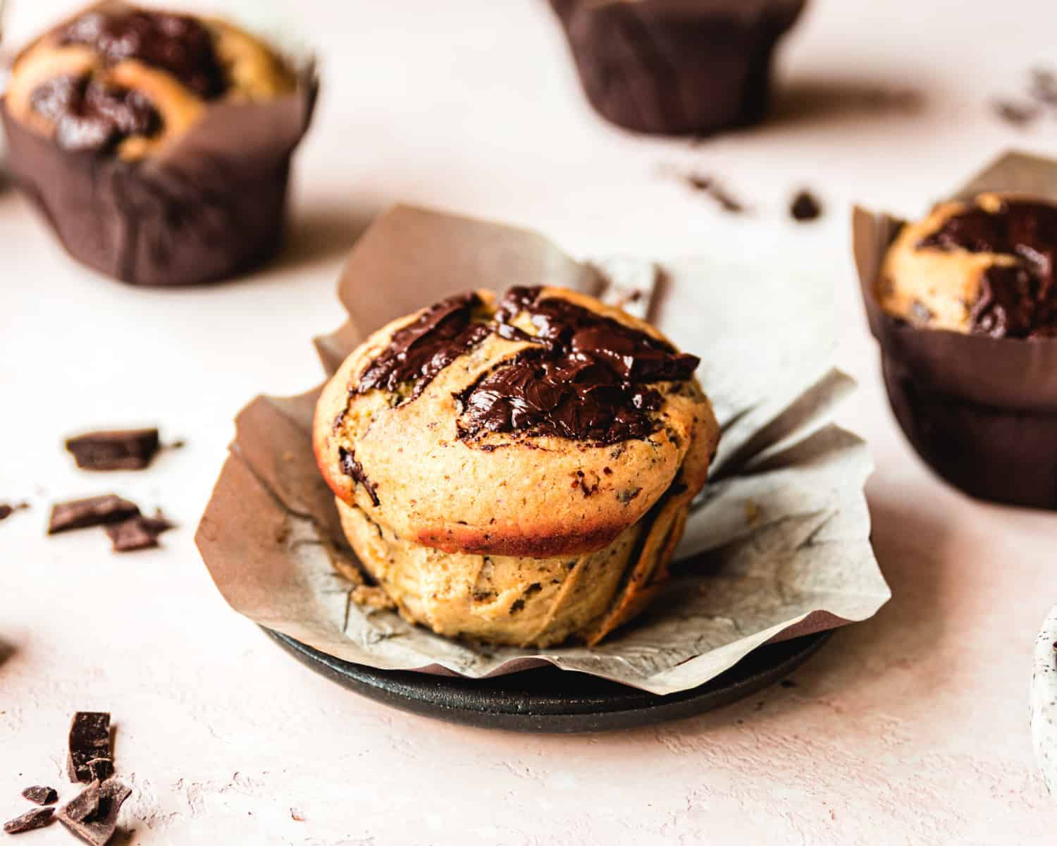 large chocolate chip muffin with paper wrapper opened on black plate