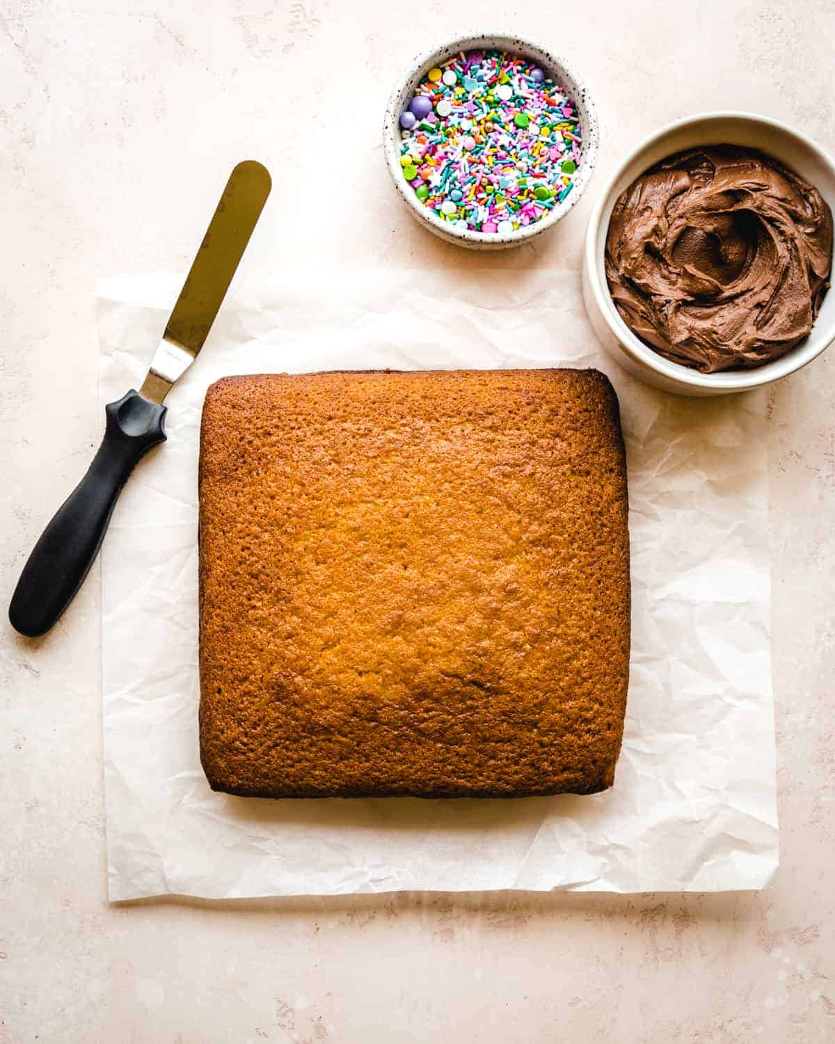 square vanilla cake getting ready to frost with a bowl of chocolate frosting an offset spatula and a bowl of rainbow sprinkles