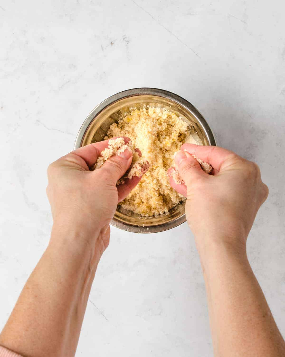 two hands mixing sugar and lemon in a metal bowl