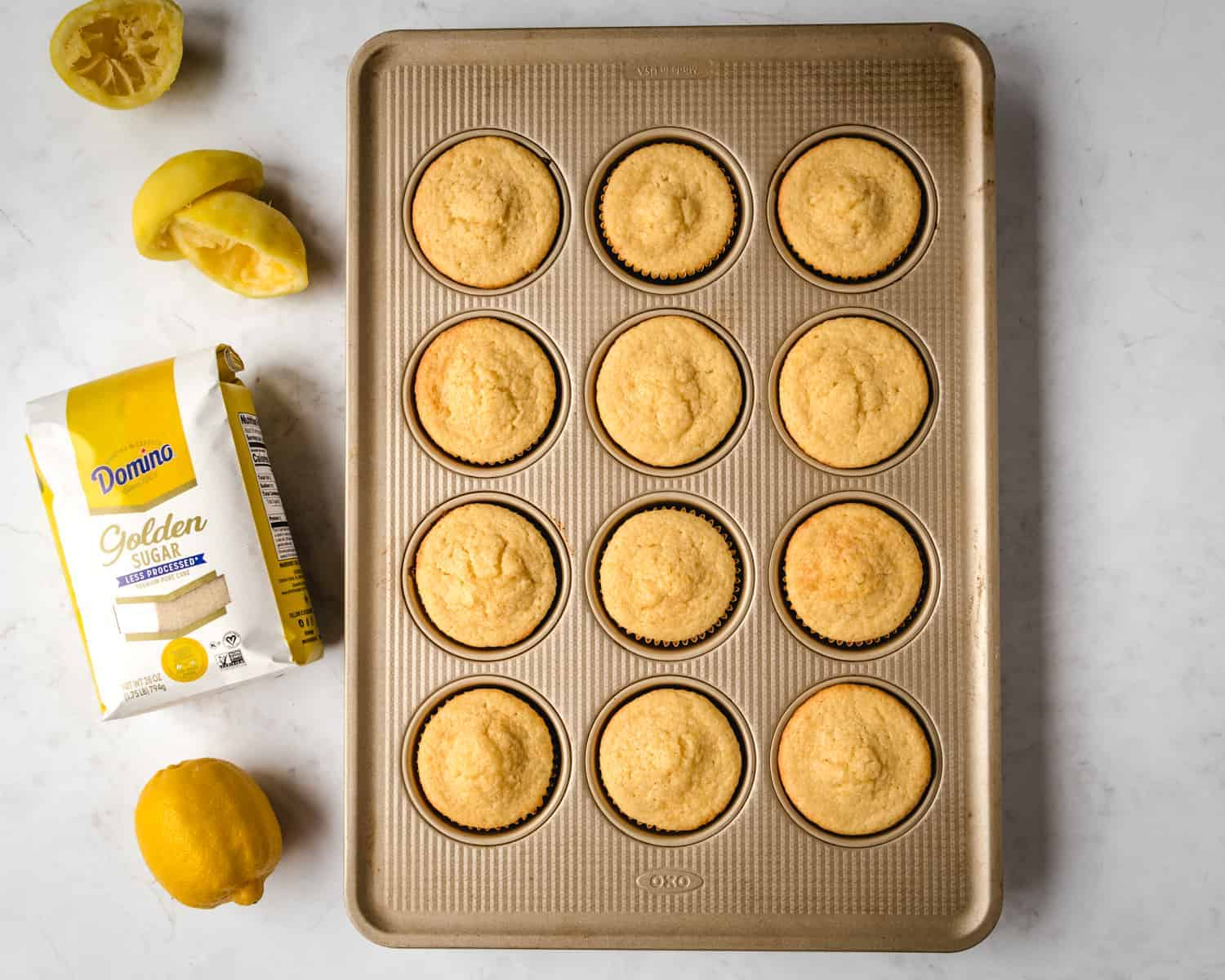 cupcakes in muffin pan with bag of sugar and lemons