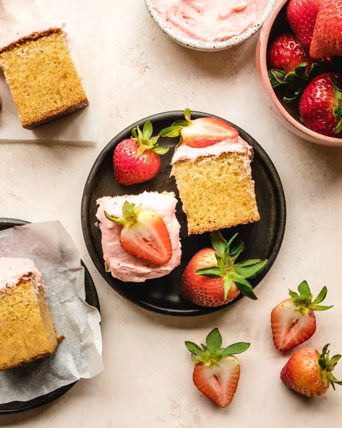 pieces of vanilla cake with strawberry frosting on a round black plate with strawberries