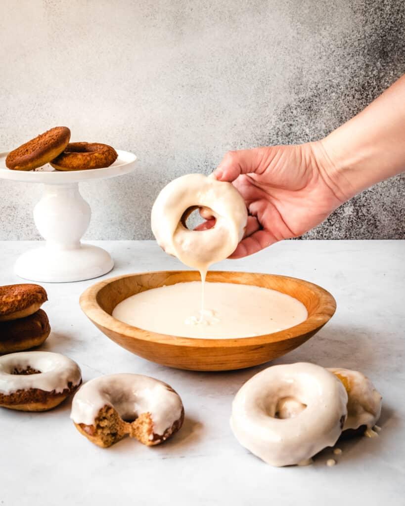 dipping a donunt in vanilla glaze
