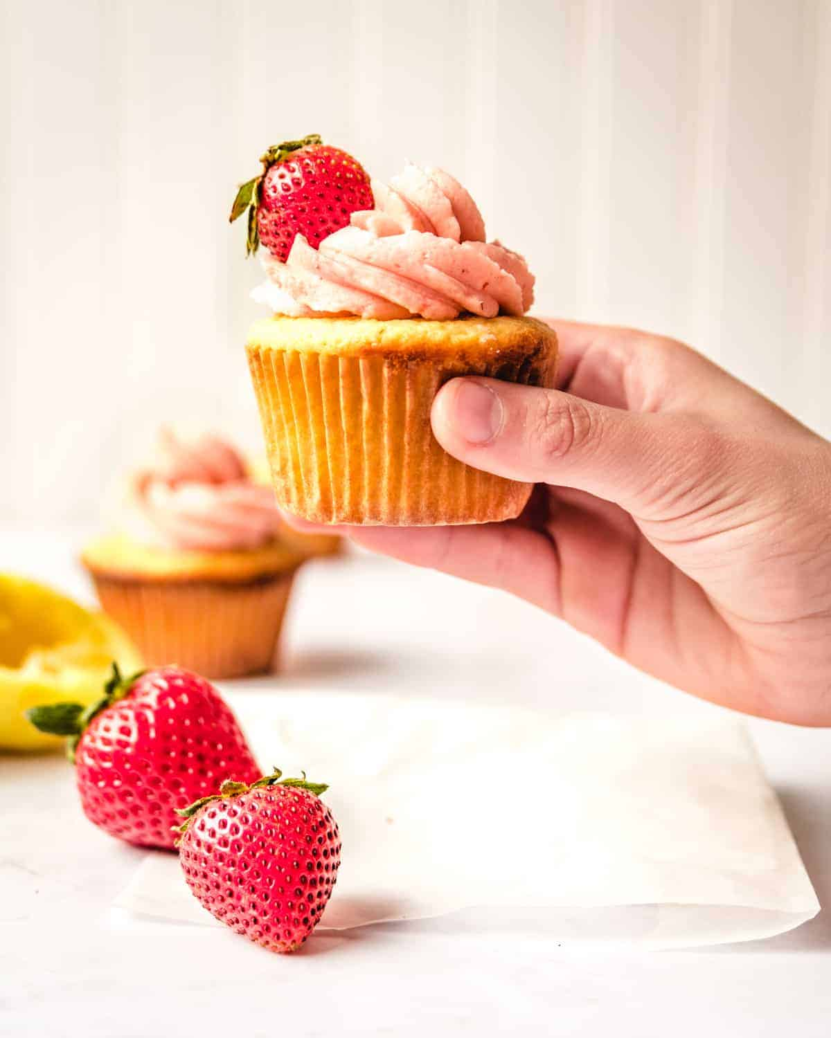hand holding lemon cupcake with strawberry on top of frosting
