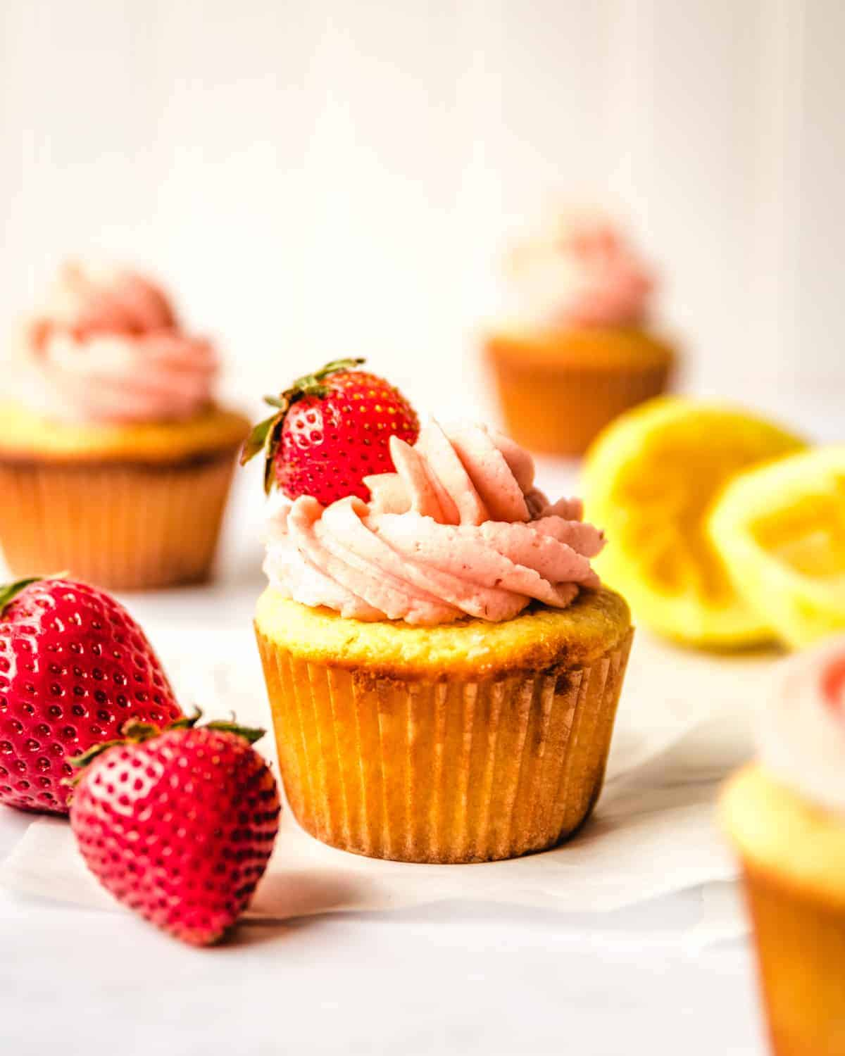 cupcake with frosting and strawberry on top with other cupcakes