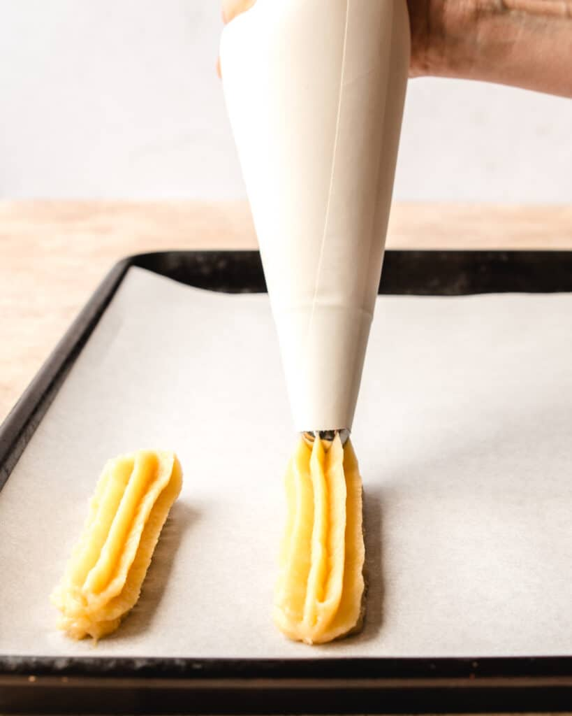 churro batter being piped out of a piping bag onto a baking sheet