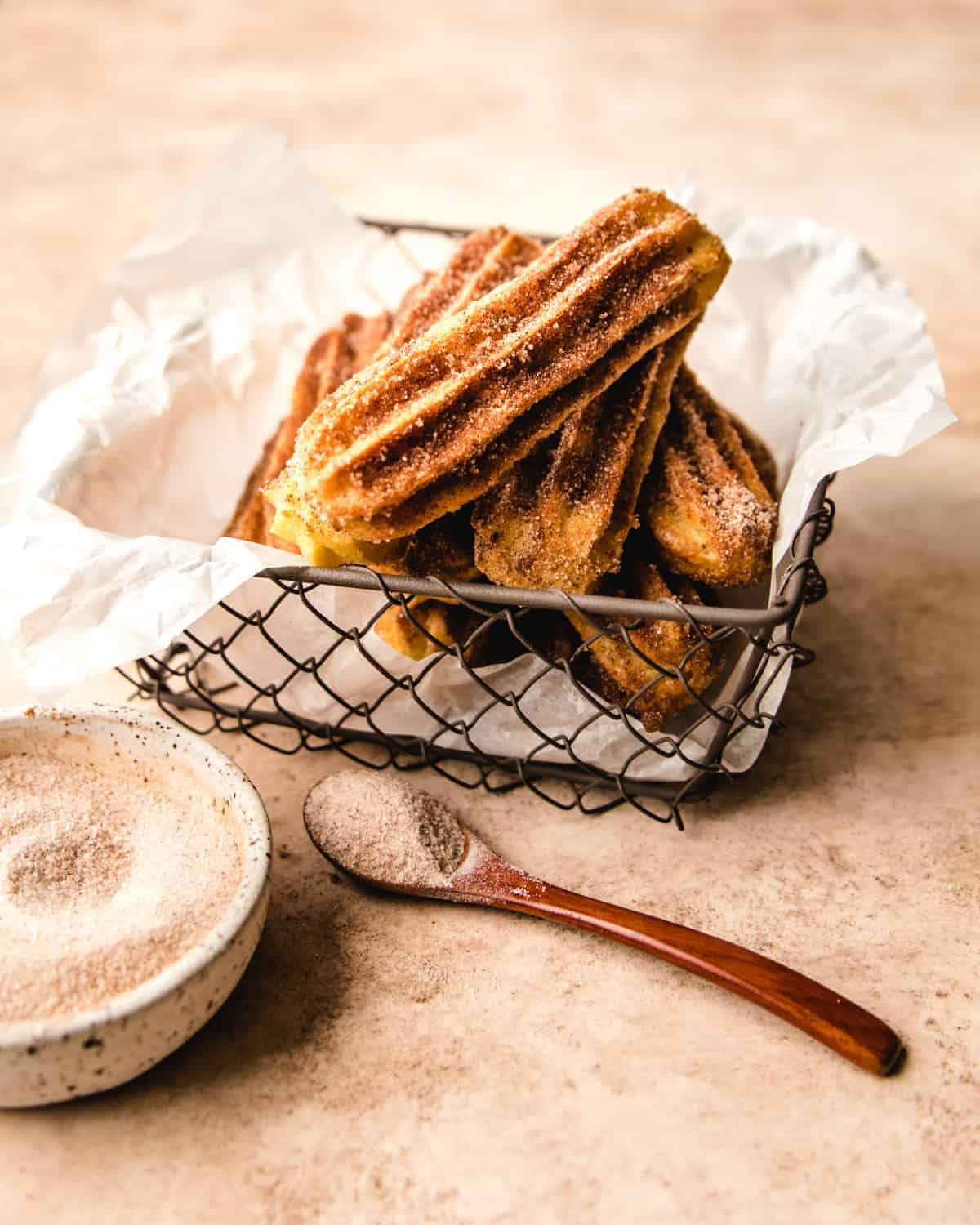 stack of churros in a metal mesh basket with paper lining with cinnamon sugar in a bowl and spoon in front