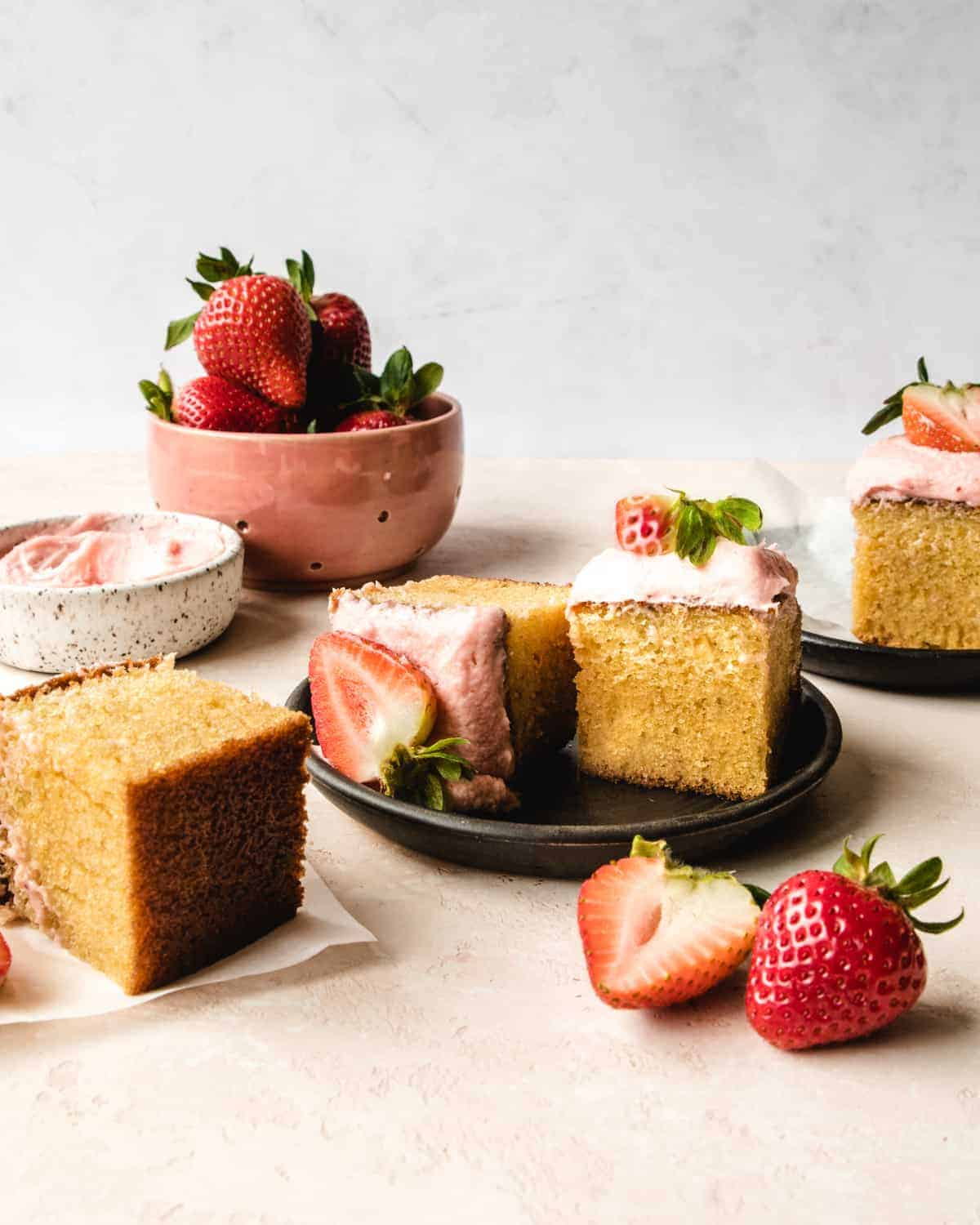 pieces of vanilla cake with strawberry frosting on plat with strawberries
