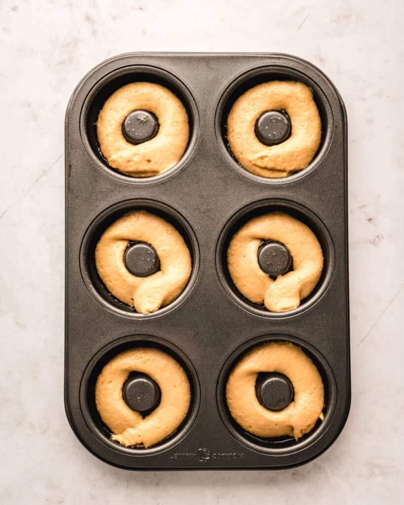 donut batter piped into donut pan ready to be baked