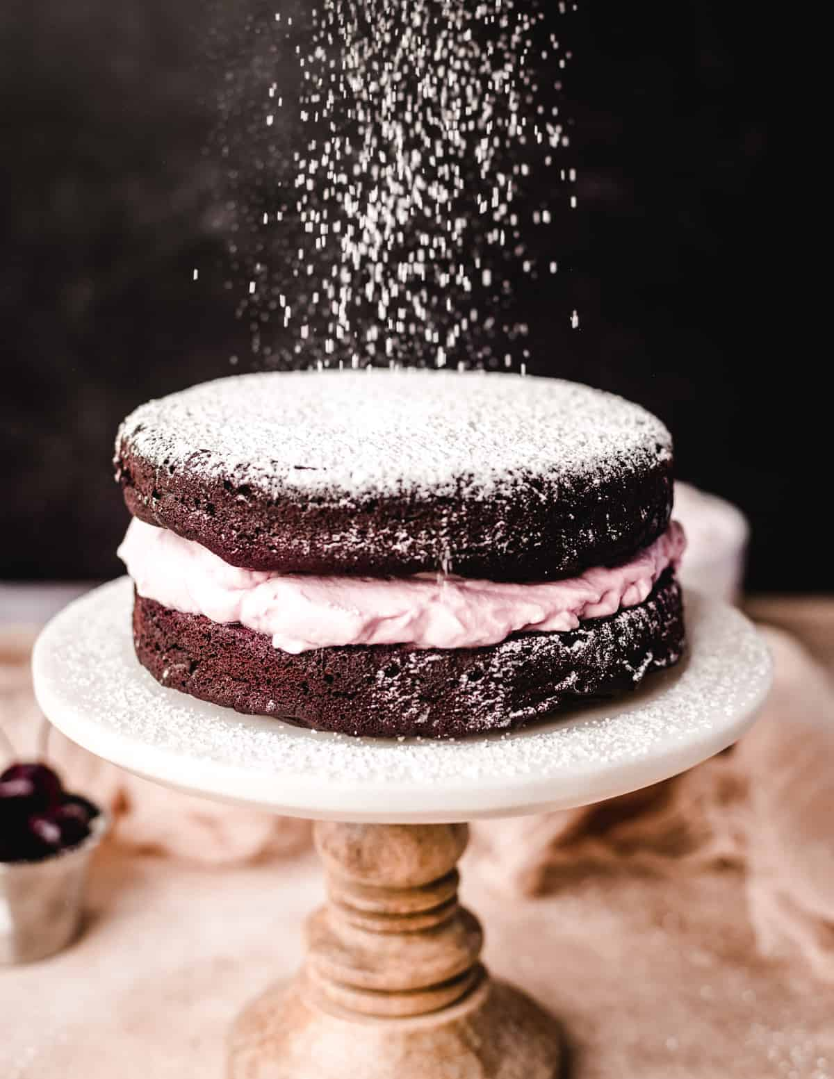 Powdered sugar is the perfect topping for this dark chocolate torte with bourbon cherry whipped cream.
