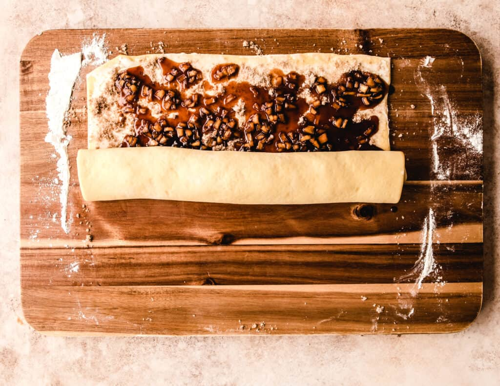 Carefully roll up the dough filled with cinnamon sugar and homemade apple pie filling.