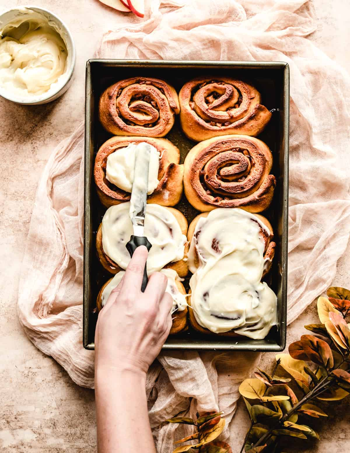 Add a nice, thick layer of cream cheese frosting to your overnight apple pie cinnamon rolls.