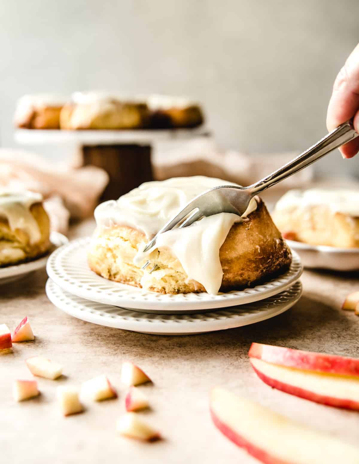 These apple pie cinnamon rolls are topped with a delicious cream cheese frosting.